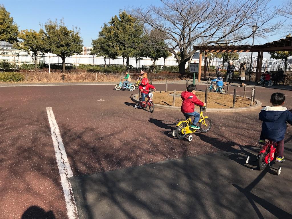 交通公園で自転車の練習をする子供(補助輪あり)