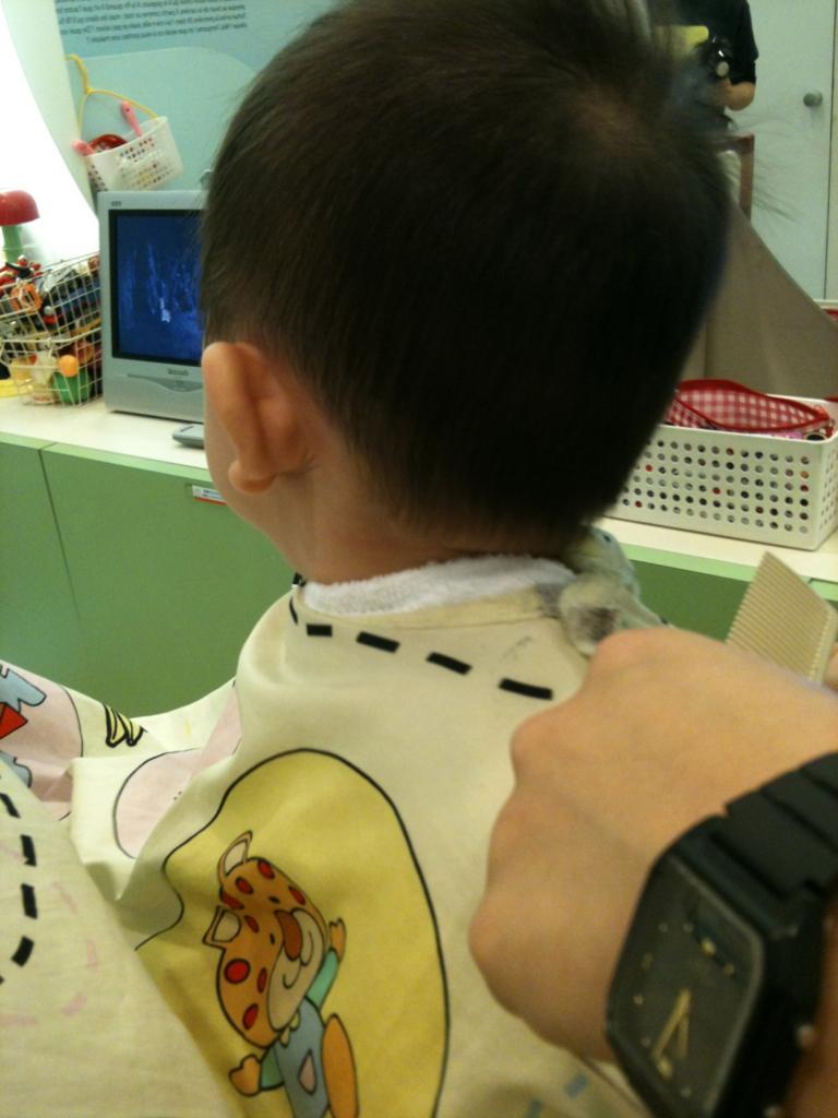 散髪屋で初めての散髪に臨む子供