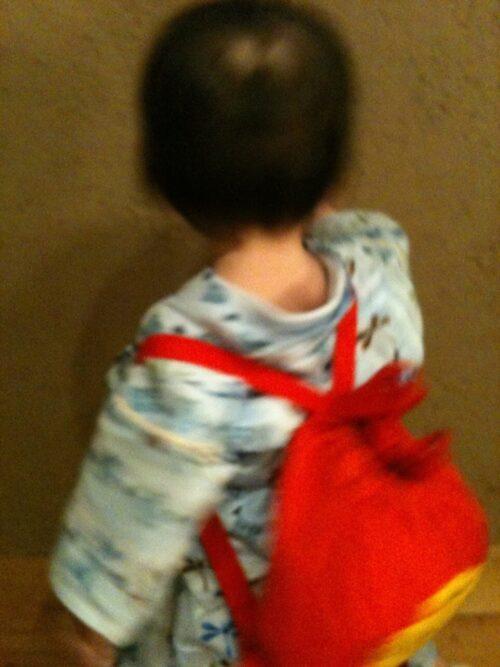 一升餅入りのリュックを背負った子供